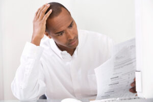 Income Tax Preparation in Newark NJ, stressed out man reviewing taxes